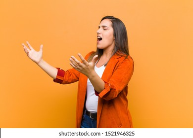 young pretty woman performing opera or singing at a concert or show, feeling romantic, artistic and passionate isolated against orange wall