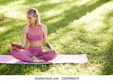 Young pretty woman in pink clothing sitting on exercise mat and using tablet pc she watching online lesson of yoga and practising it outdoors