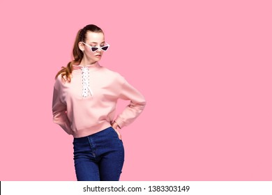young pretty woman in pink sweater and sunglasses isolated on pink studio background.