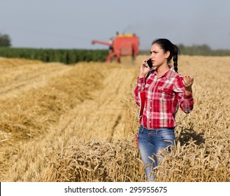 Young pretty woman in plaid shirt standing in ripe wheat field and talking on cell phone, combine harvesting in background