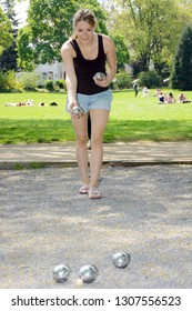 Young pretty woman is playing boule in the park on a sunny summer day