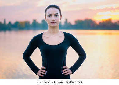 Young pretty woman portrait in early morning at colorful sunrise background