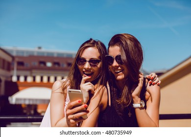 young pretty woman posing in the street with phone, outdoor portrait, hipster girls, sisters, chic, tablet, internet, using smartphone, close-up fashion model, post in social cell, holding, selfie,USA