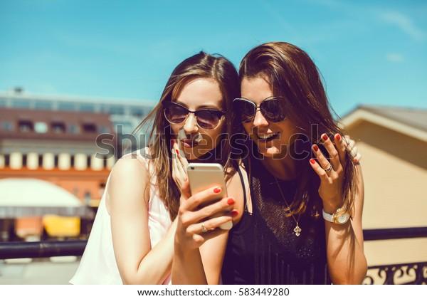 giovane bella donna in posa per strada con telefono, ritratto all'aperto, ragazze hipster, sorelle, chic, tablet, Internet, utilizzando lo smartphone, modello di moda Close-up, post in instagram, Facebook