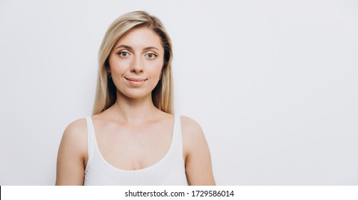 Young pretty woman with professional make-up applied, against a light background