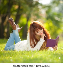 Young pretty woman read electronic book in the park. Beauty nature scene with colorful spring background. Outdoor lifestyle. Happy smiling woman relax with tablet on green grass