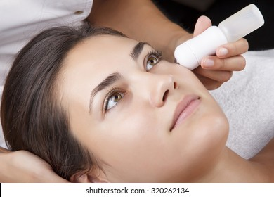 Young pretty woman receiving treatments in beauty salons. Young beautiful dark-haired woman in the office beautician lying on the couch. Electroporation procedure. Hardware cosmetology.