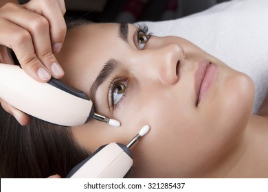 Young pretty woman receiving treatments in beauty salons. Young beautiful dark-haired woman in the office beautician lying on the couch. Miostimulation procedure. Hardware cosmetology.