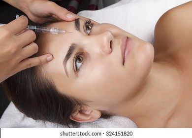 Young pretty woman receiving treatments in beauty salons. Young beautiful dark-haired woman in the office beautician lying on the couch. Contouring procedure , revitalization. Beauty injections .