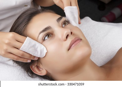 Young pretty woman receiving treatments in beauty salons. Young beautiful dark-haired woman in the office beautician lying on the couch. The procedure for cleaning the face