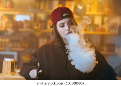 Young pretty woman in red cap smoke an electronic cigarette at the vape shop. Hip-hop style. Closeup.