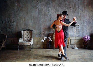 Young pretty woman in red dress and man in black suit dance tango