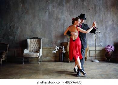 Junge hübsche Frau in rotem Kleid und Mann in schwarzem Anzug Tango