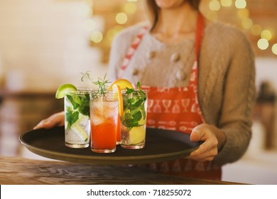 Young pretty woman with red and green cocktails on tray in the bar