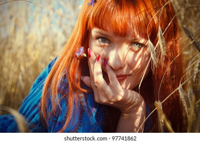 Young pretty woman with red hair at the field of wheat