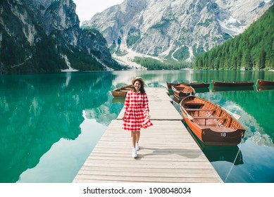 young pretty woman red sundress walking by wooden wharf with boats. summer vacation. mountain lake on background