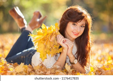 Young pretty woman relaxing in the autumn park. Beauty nature scene with colorful foliage background, yellow trees and leaves at fall season. Autumn outdoor lifestyle