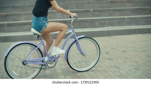 Young pretty woman riding bicycle in city