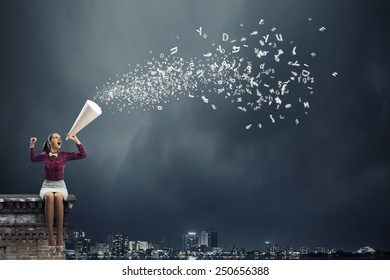 Young pretty woman screaming in paper trumpet