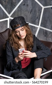 young pretty woman or sexy girl with long hair in black cap and sneakers sitting in gesometric chair with mobile or cell phone on grey background