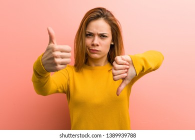 Young pretty young woman showing thumbs up and thumbs down, difficult choose concept