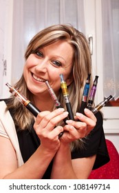 Young pretty woman shows multiple e-cigarettes and smiles
