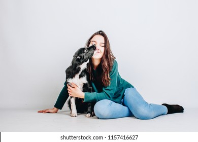 Young pretty woman sits together with her border collie dog and hugs it isolated on white background. Dog licks owner. Studio portrait.