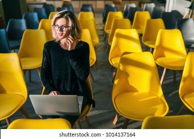 young pretty woman sitting alone in co-working office, conference room, many yellow chairs, working at laptop, sunny, backlight, talking on phone, communication