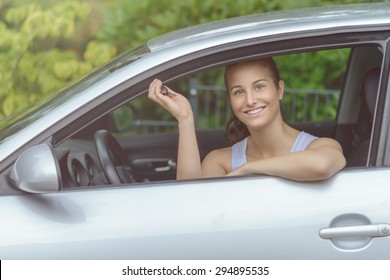Young Pretty Woman Sitting Inside her Car, Smiling at the Camera While Showing Keys on her Hand.
