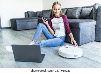 Young pretty woman sitting on the floor with laptop and control robot vacuum cleaner from the phone