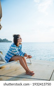 young pretty woman sitting on sun lounger looking at sunset over the sea. copy space