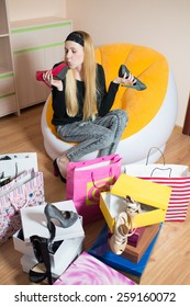 Young pretty woman sitting on a chair and kissing women's shoes. Woman on the shopping