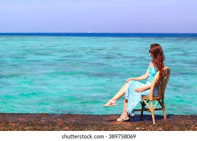 young pretty woman sitting on a bamboo chair on the beach
