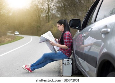 Young pretty woman sitting on suitcase beside car and looking at map on road. Lost on trip, worried face