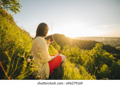 young pretty woman sitting on the peak of the hill and looking at city landscape while drinking coffee with chocolate