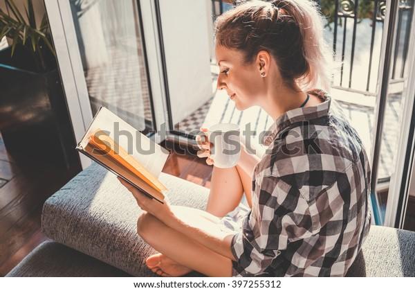 Junge hübsche Frau im geöffneten Fenster, die Kaffee trinkt und ein Buch liest, genießt Ruhe