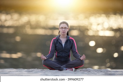 Young pretty woman sitting in yoga position on sandy coast and meditating. Sunshine reflection on the water surface in background