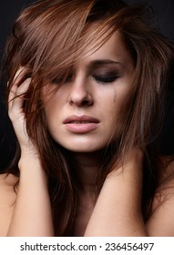 Young pretty woman with smeared mascara crying on black background
