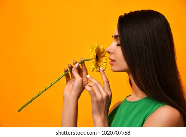 Young pretty woman smell yellow gerbera flower in green dress with closed eyes