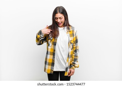 young pretty woman smiling cheerfully and casually, looking downwards and pointing to chest isolated against white wall