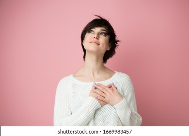Young pretty woman smiling with hands on chest and grateful gesture on face, looking up with hope. Happy woman feels grateful, believes in success, wishes dream come true, visualizes future.