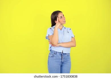 joven y bonita mujer sonriendo alegremente mirando a la derecha y pensando en algo contra la pared amarilla