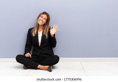 young pretty woman smiling happily and cheerfully, waving hand, welcoming and greeting you, or saying goodbye business concept