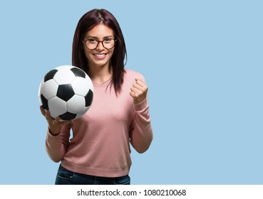 Young pretty woman smiling and happy, holding a soccer ball, competitive attitude, excited to play a game