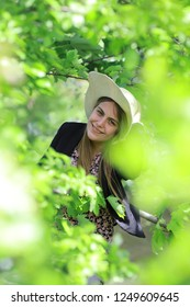 Young and pretty woman smiling with a hat with a green nature background