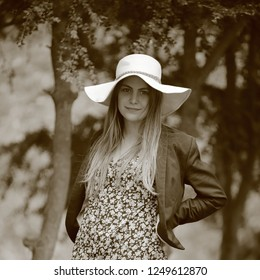 Young and pretty woman smiling with a hat with a nature background