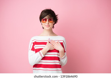 Young pretty woman  smiling and looking to camera with hands on chest and grateful gesture on face. Happy smiling woman feels grateful, hopes for successful plan realization, believes in success, wish