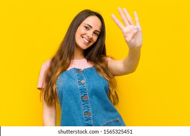 young pretty woman smiling and looking friendly, showing number four or fourth with hand forward, counting down
