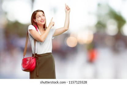 young pretty woman smiling and pointing upwards with both hands, towards the place where the publicist may show a concept.
