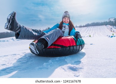 young pretty woman smiling snow tubing. slide from winter hill. christmas activity concept
